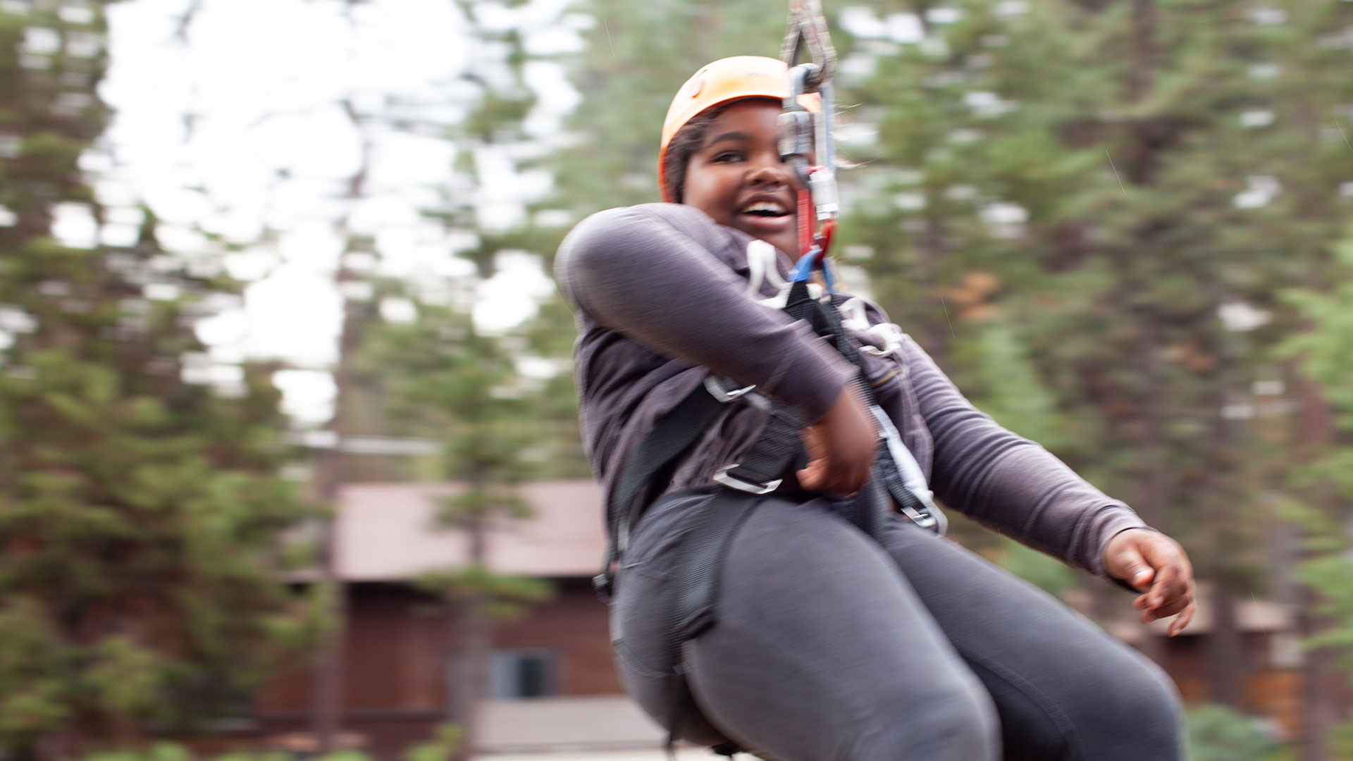 girl smiling on zipline in forest