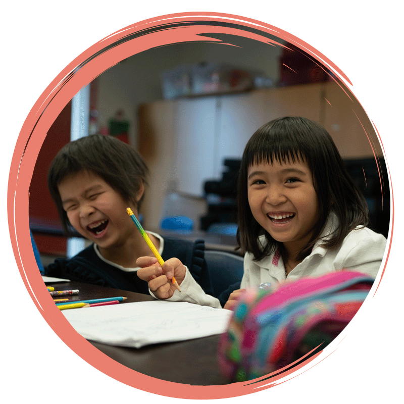 Girl students laughing together during dual language class