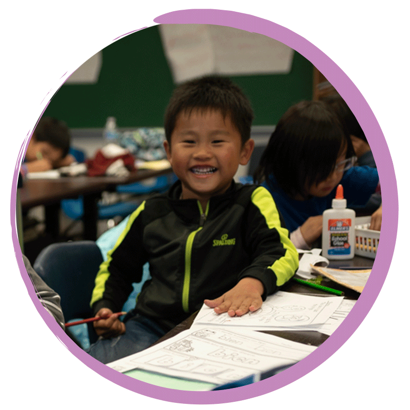 Little boy student smiling during dual language class
