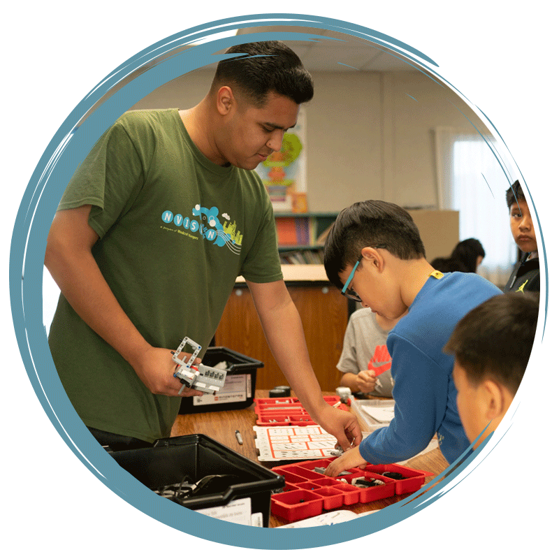 staff member working with students on robotics projects
